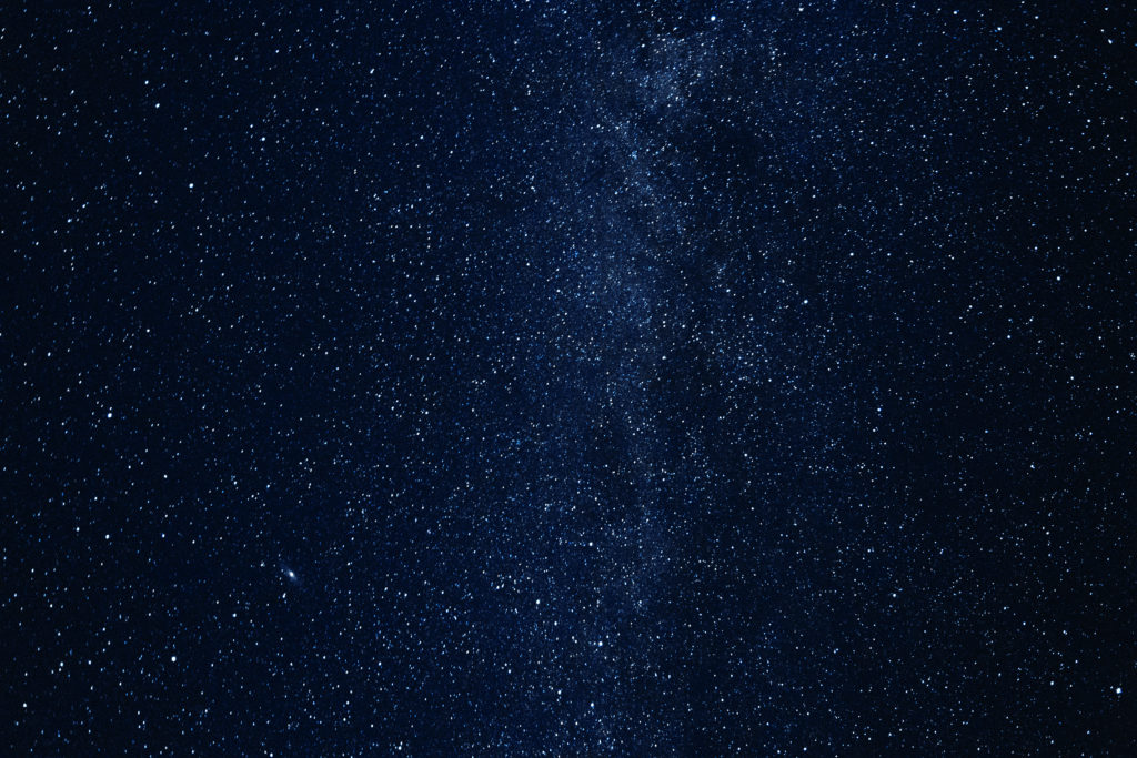 Milky way galaxy with glowing stars and planets in the universe. Dark blue sky in the night