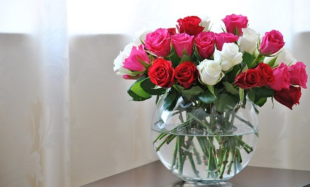 A Rose bowl vase containing red, pink and white Roses, photographed on a wooden table with emphasis on diffused light.